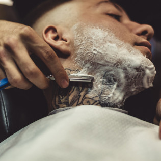 Man getting his beard shaved in Buffalo, NY